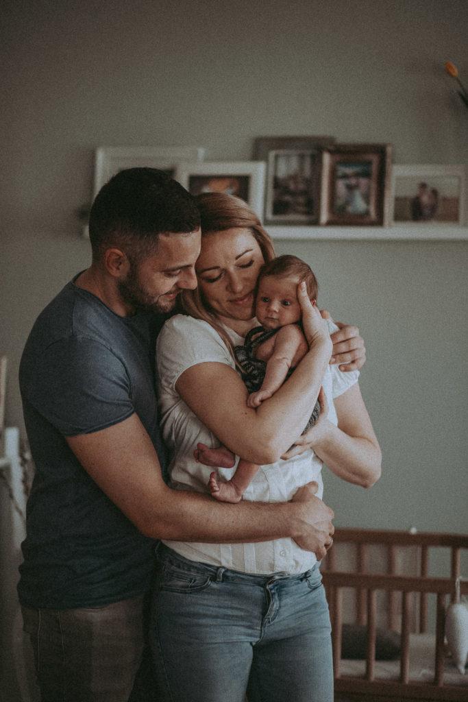 Newborn Shooting, Mann und Frau stehen eng umschlungen mit einem Neugeborenen auf dem Arm im Kinderzimmer