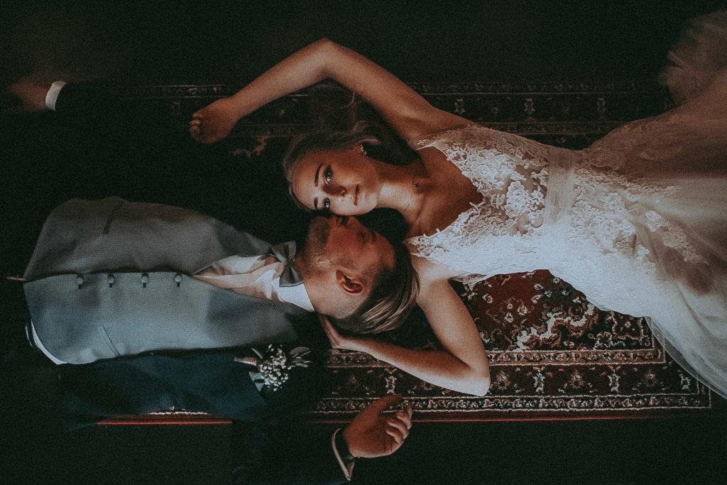 hochzeitsfoto eines brautpaares rücklings auf dem boden liegend. braut schaut nach oben in die kamera, bräutigam küsst braut auf die wange