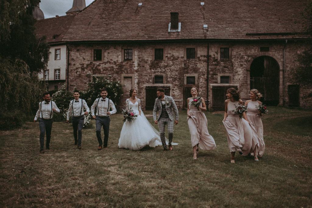 Foto von Braut und Bräutigam mit Trauzeugen und Brautjungfern auf einer Wiese vor einem alten Farmhaus.