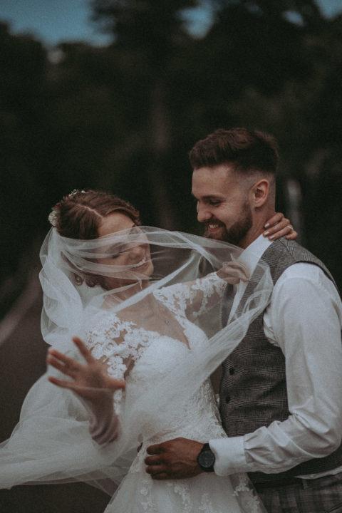 lachendes Brautpaar tanzend auf einer Wiese, Braut wirbelt Schleier