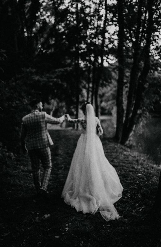 Hochzeitsfoto in schwarz-weiß. Fernaufnahme Brautpaar von hinten fotografiert im Wald