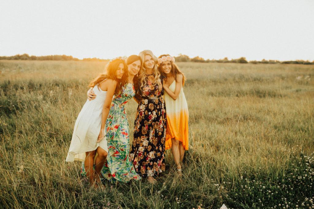 Foto von vier Frauen in Kleidern bei Sonnenuntergang auf einer Wiese