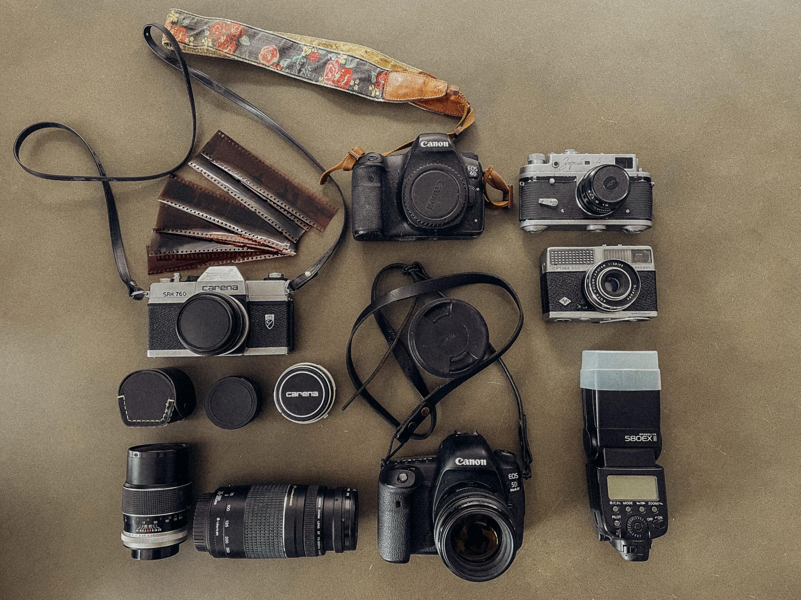 Flatlay von einem Foto-Equiptment bestehend aus Kameras, Objektiven und einem Kamerablitz